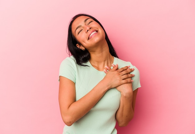 Young venezuelan woman isolated on pink background has friendly expression, pressing palm to chest. love concept. Premium Photo