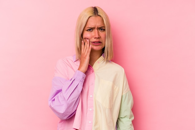 Young venezuelan woman isolated on pink background having a strong teeth pain, molar ache.