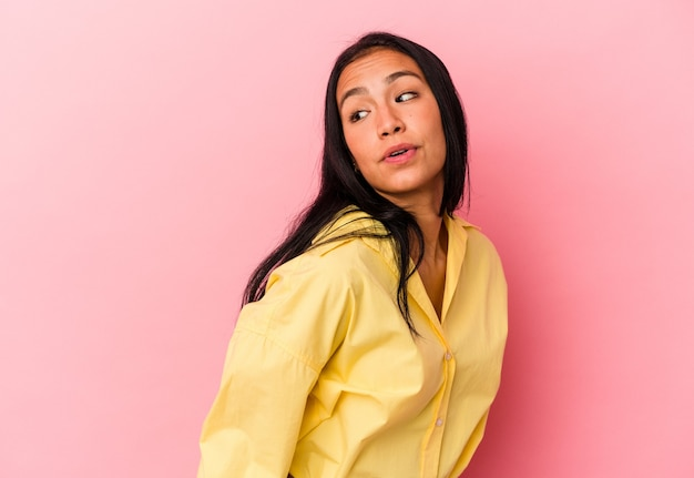 Young venezuelan woman isolated on pink background looks aside smiling, cheerful and pleasant.