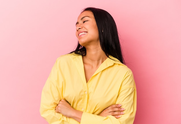 Young venezuelan woman isolated on pink background smiling confident with crossed arms.