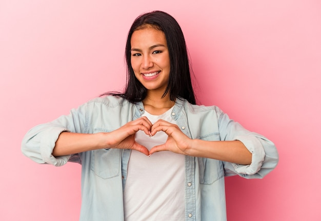 Young venezuelan woman isolated on pink background smiling and showing a heart shape with hands. Premium Photo