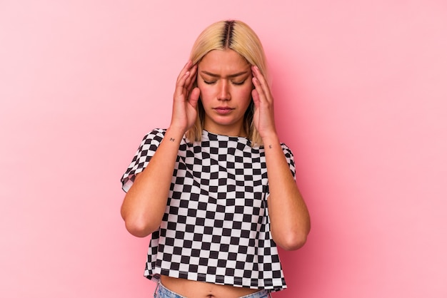 Young venezuelan woman isolated on pink background touching temples and having headache.