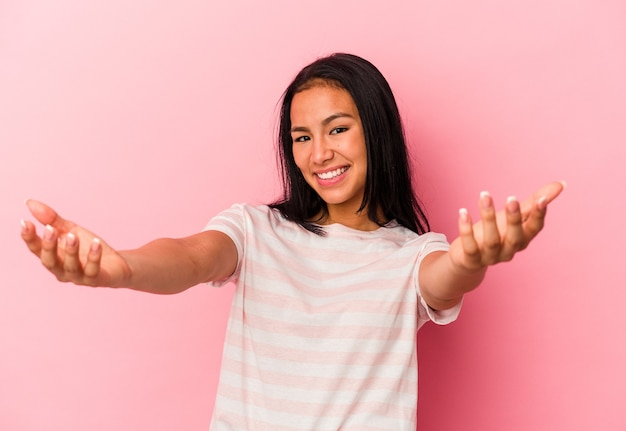 Young venezuelan woman isolated on pink wall feels confident giving a hug