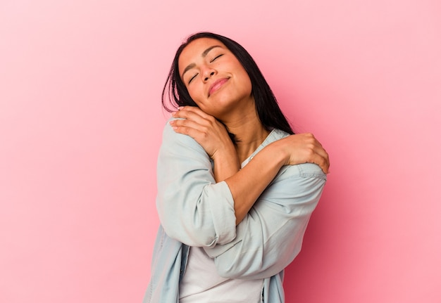 Young venezuelan woman isolated on pink wall hugs, smiling carefree and happy.