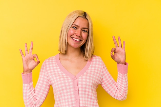 Young venezuelan woman isolated on yellow background cheerful and confident showing ok gesture.