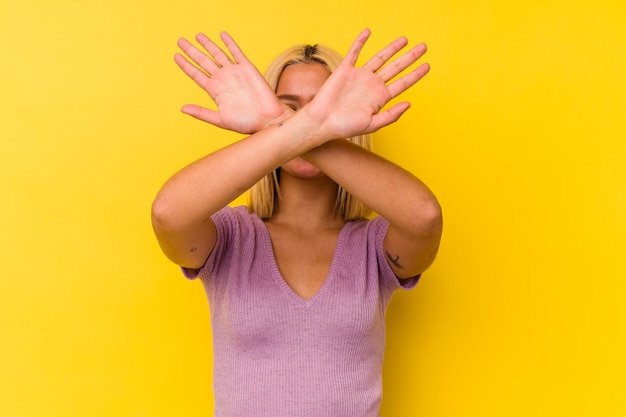 Young venezuelan woman isolated on yellow background keeping two arms crossed, denial concept.