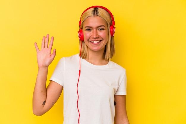 Молодая венесуэльская женщина, слушающая музыку на желтом фоне, улыбается веселый, показывая номер пять с пальцами.
