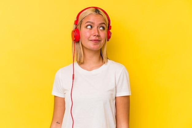 목표와 목적을 달성하는 꿈을 꾸고 노란색 벽에 고립 된 젊은 베네수엘라 여자 듣는 음악
