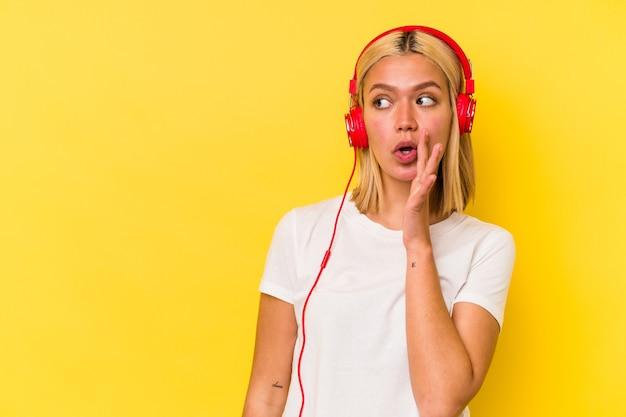 노란색 벽에 고립 된 젊은 베네수엘라 여자 듣는 음악은 비밀 뜨거운 제동 뉴스를 말하고 옆으로보고