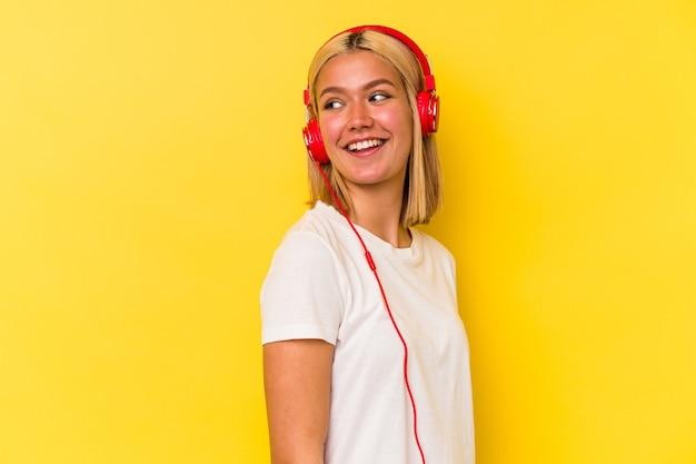 노란색 벽에 고립 된 젊은 베네수엘라 여자 듣기 음악은 옆으로 웃고, 밝고 쾌적한 보인다