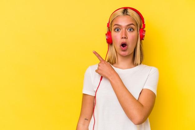 측면을 가리키는 노란색 벽에 고립 된 젊은 베네수엘라 여자 듣기 음악