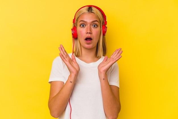 노란색 벽에 고립 된 젊은 베네수엘라 여자 듣기 음악 놀라게 하 고 충격