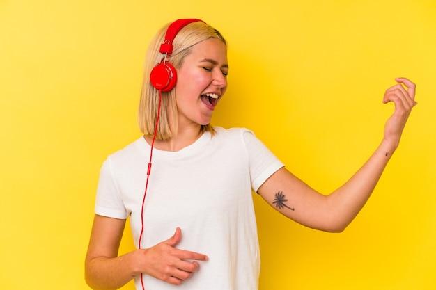 노란색 벽에 고립 된 젊은 베네수엘라 여자 듣기 음악
