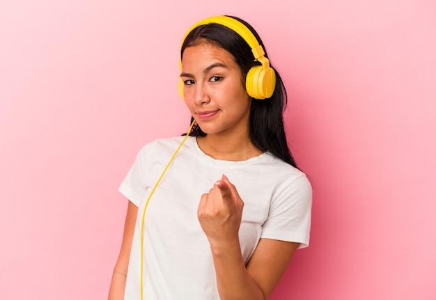 ピンクの背景で隔離された音楽を聞いている若いベネズエラの女性は、招待が近づくようにあなたに指を指しています。