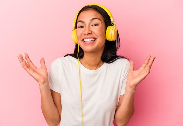 ピンクの背景に分離された音楽を聞いている若いベネズエラの女性は、嬉しい驚き、興奮し、手を上げています。