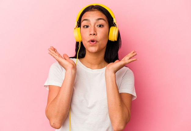 ピンクの背景に分離された音楽を聞いている若いベネズエラの女性は驚いてショックを受けました。