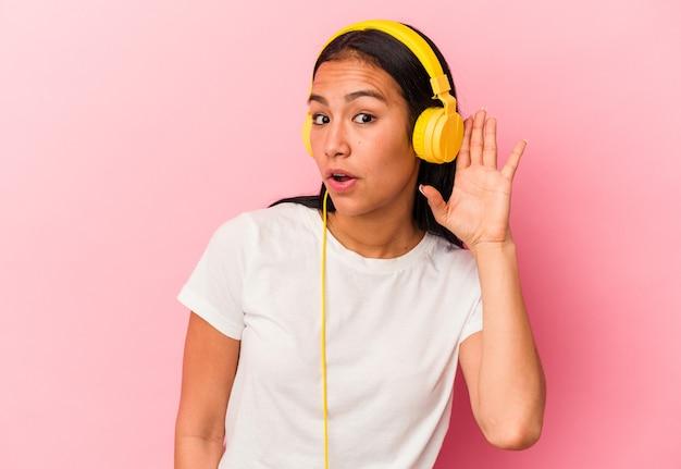ゴシップを聴こうとしているピンクの背景に分離された音楽を聞いている若いベネズエラの女性。