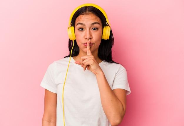 秘密を守るか、沈黙を求めてピンクの壁に隔離された音楽を聞いている若いベネズエラの女性。