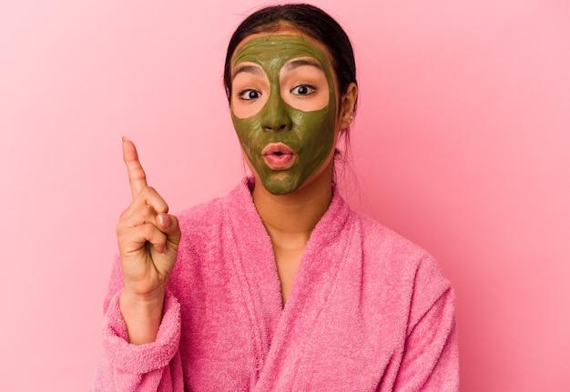 いくつかの素晴らしいアイデア、創造性の概念を持っているピンクの背景で隔離のバスローブと顔のマスクを身に着けている若いベネズエラの女性。