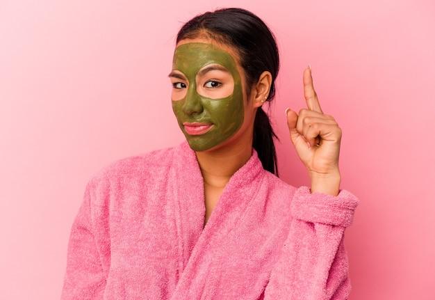 ピンクの背景に隔離されたバスローブと顔のマスクを身に着けている若いベネズエラの女性は、指で寺院を指して、考えて、タスクに焦点を当てました。