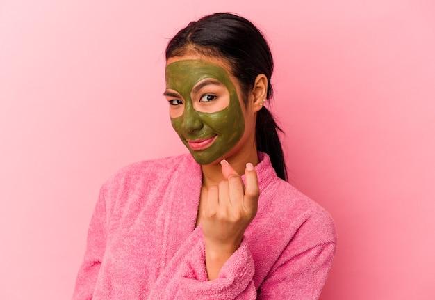ピンクの背景に隔離されたバスローブと顔のマスクを身に着けている若いベネズエラの女性は、招待が近づくようにあなたに指を指しています。