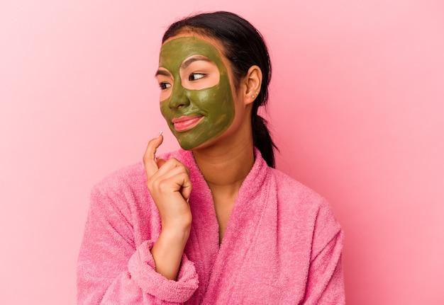 ピンクの背景に分離されたバスローブと顔のマスクを身に着けている若いベネズエラの女性は、コピースペースを見ている何かについて考えてリラックスしました。