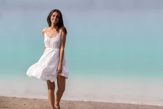 Young very beautiful girl with long hair in a white dress by the lake.