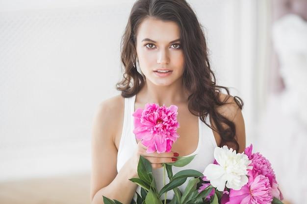 屋内の花を持つ若い非常に美しい女性。魅力的な女性のクローズアップの肖像画。