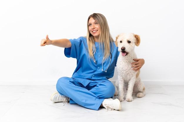 親指を立てるジェスチャーを与える床に座っている犬と若い獣医の女性