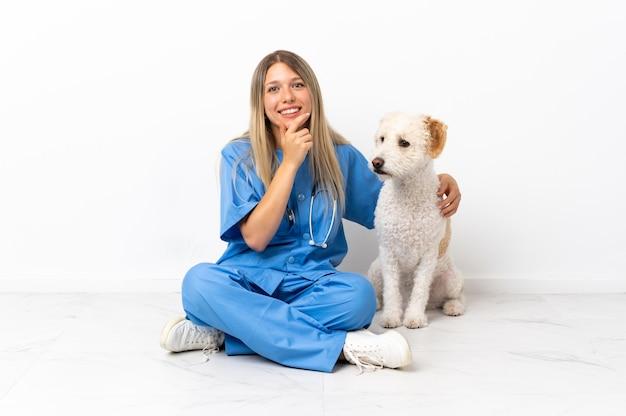 横を向いて笑って床に座っている犬と若い獣医の女性