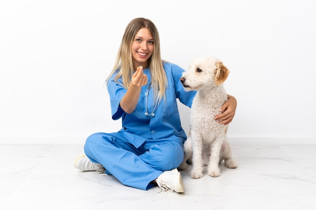 Молодая ветеринарная женщина с собакой сидит на полу и делает денежный жест