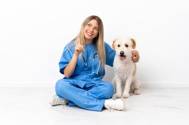 素晴らしいアイデアを指している床に座っている犬と若い獣医の女性