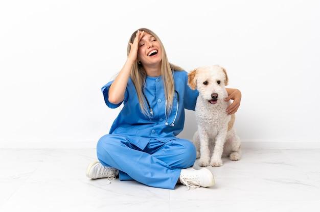 たくさん笑って床に座っている犬と若い獣医の女性