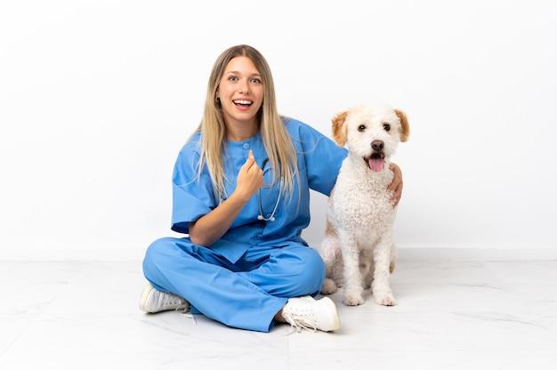驚きの表情で床に座っている犬と若い獣医の女性