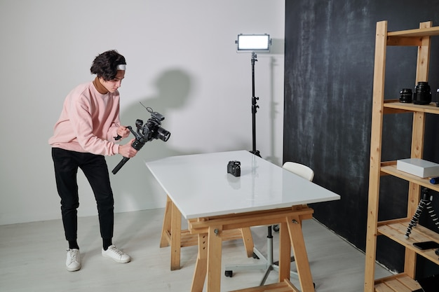 Young video blogger in casualwear shooting new photo equipment while standing by desk in studio