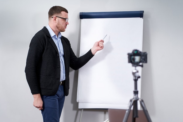 Young video blogger presenting important data on empty flipchart mockup, online education concept