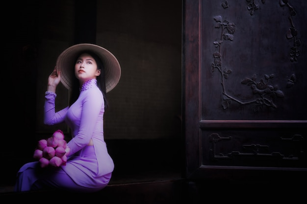 Young vietnam woman wearing ao dai culture traditional at old temple at ho chi minh in vie