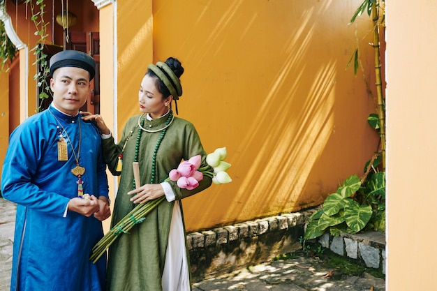 야외에 서 있는 전통적인 아오자이 드레스를 입은 젊은 베트남 신부와 신랑