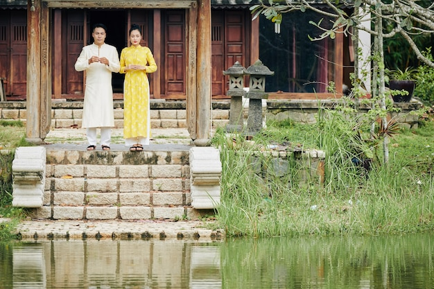 사원 앞에 향을 들고 서 있는 아오자이 드레스를 입은 젊은 베트남 부부
