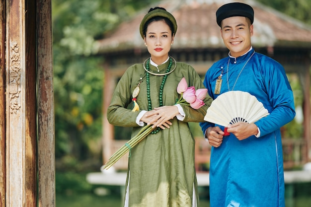 국복을 입은 젊은 베트남 부부는 연꽃과 조각된 부채를 들고 야외에 서서 카메라를 보며 웃고 있다