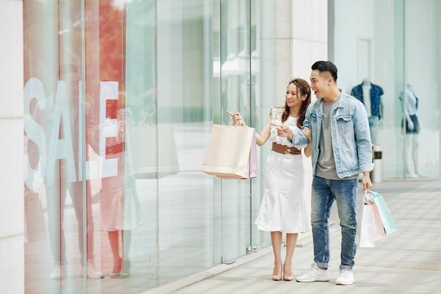 Молодая вьетнамская пара делает покупки в торговом центре на неделе, гуляет и смотрит в витрину