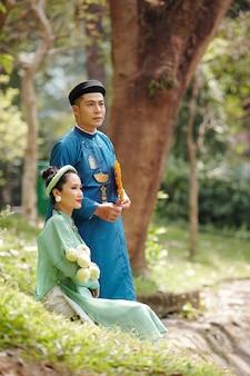 화창한 날 공원에서 쉬고 있을 때 전통 아오자이 드레스를 입은 젊은 베트남 부부
