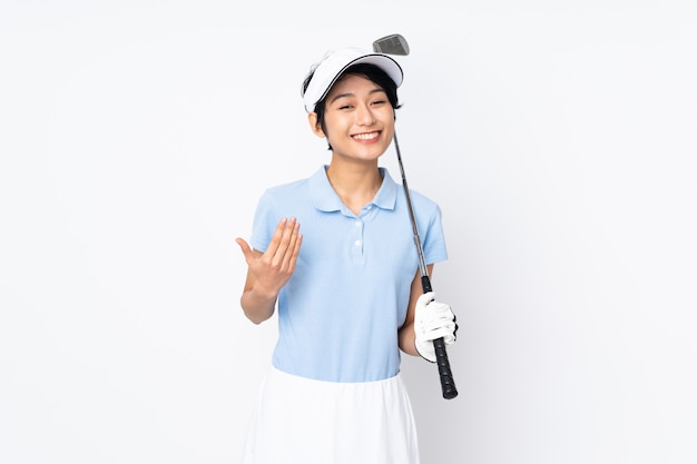 Young vietnamese golfer woman over isolated white wall playing golf and doing coming gesture