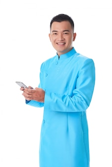 Young vietnamese man in traditional attire posing in studio and using smartphone