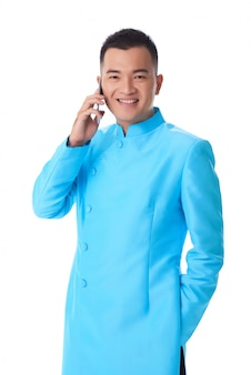Young vietnamese man in traditional long turquioise jacket talking on mobile phone