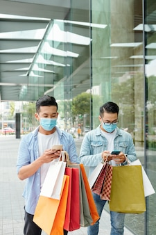Young vietnamese men in medical masks walking in the street with shopping bags and texting friends or checking notifications