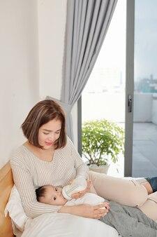 Молодая вьетнамская женщина кормит маленькую дочь формулой в бутылке