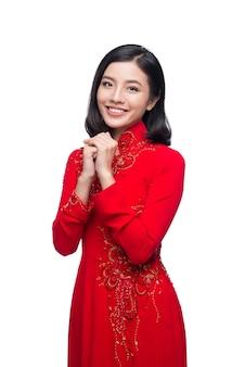 Молодая вьетнамская женщина в платье ао дай с молитвенным жестом желает вам удачи