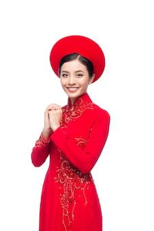 あなたに幸運を祈るジェスチャーでアオザイのドレスを着た若いベトナム人女性