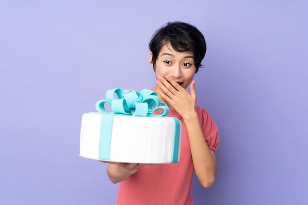 Молодая вьетнамская женщина с короткими волосами держит большой торт на изолированных фиолетовый с удивлением и шокирован выражением лица